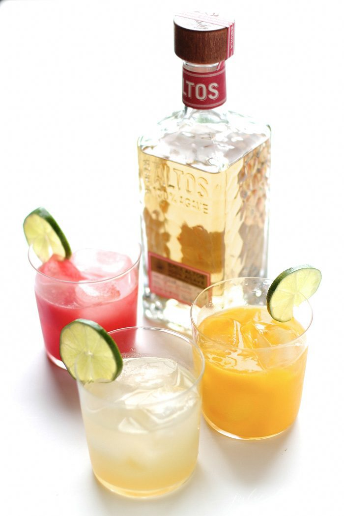 Three cocktails in front of a bottle of tequila