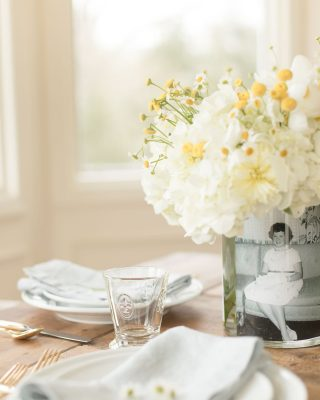 A table set with mother's day decorations of a simple vase of flowers with a vintage photo inside.