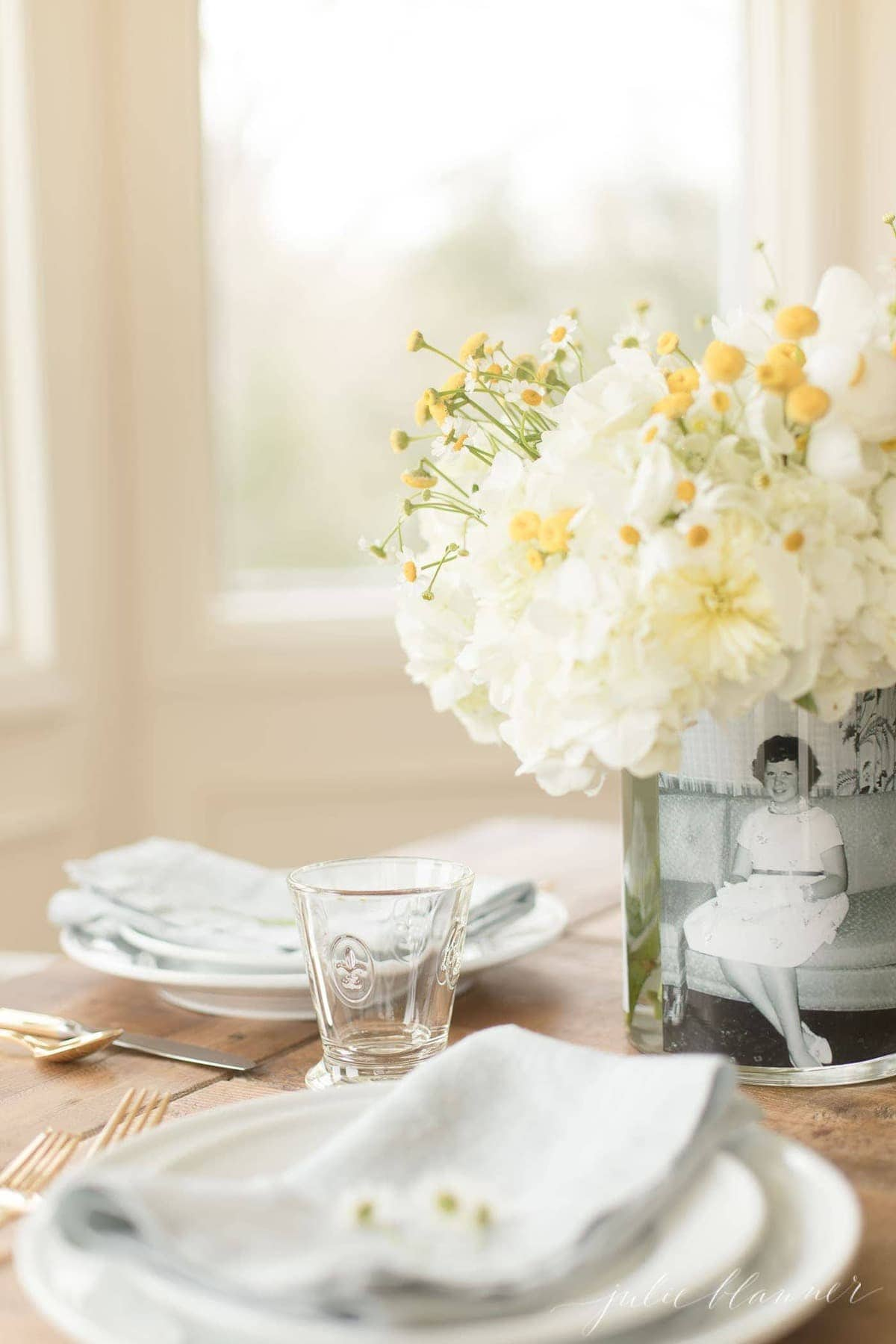 mother's day photo centerpiece on table set with white dishes and glassware