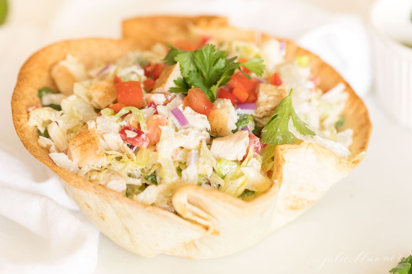 A chicken taco salad topped with tomatoes and cilantro in a tortilla bowl.