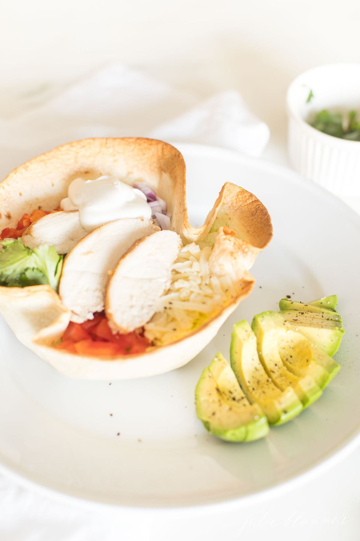 A tortilla bowl full of chicken, cheese, lettuce and more, on a white plate