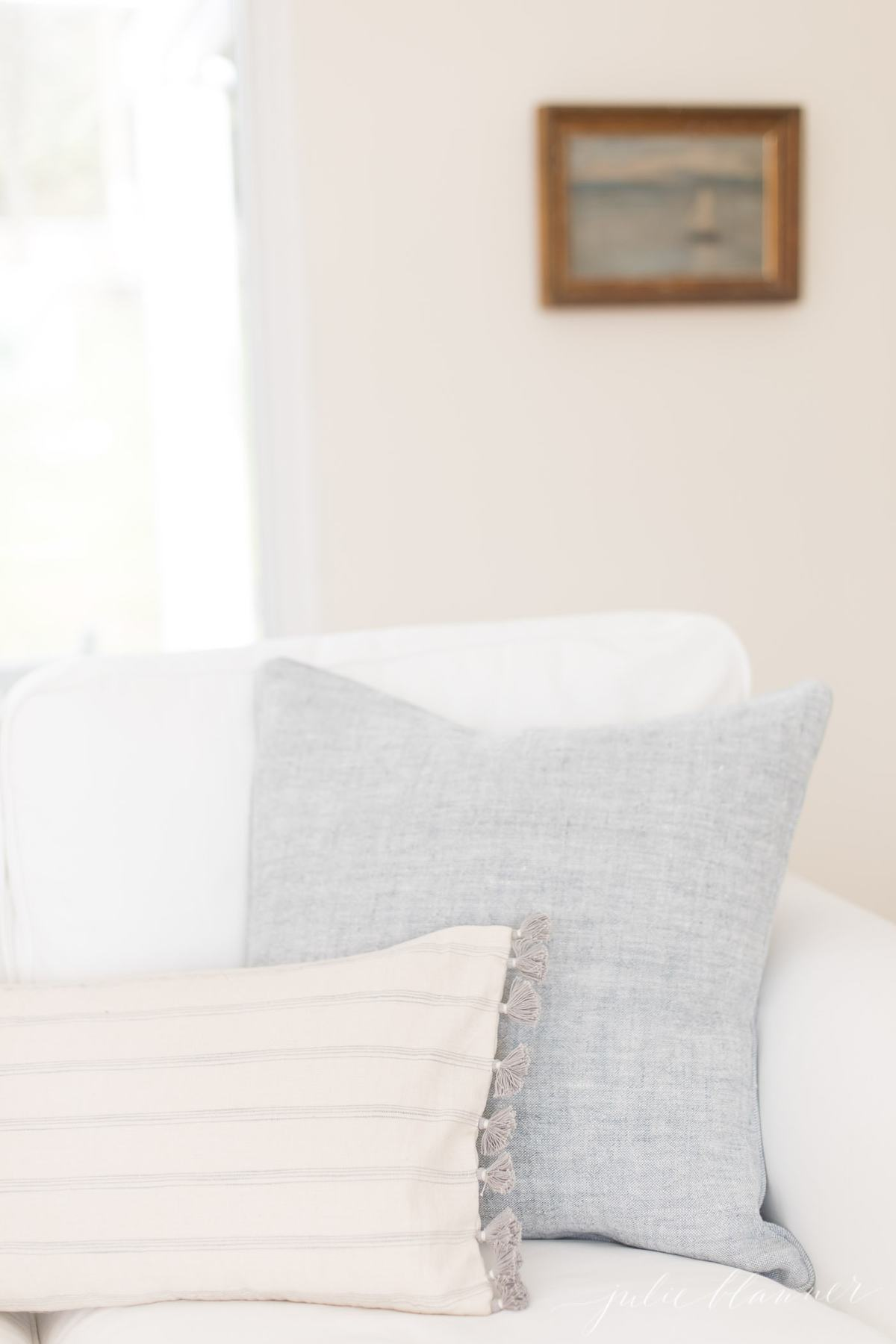 A white sofa with a blue pillow in a living room, in a post about an easy way to get rid of smoke smell