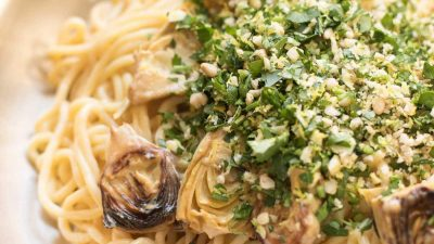 spaghetti in a skillet with artichokes topped with gremolata