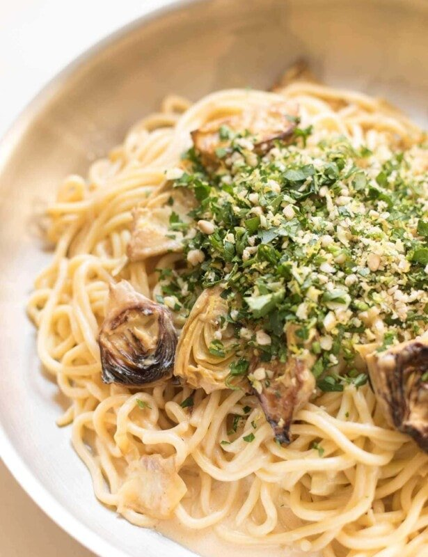 spaghetti in a skillet with artichokes topped with gremolata