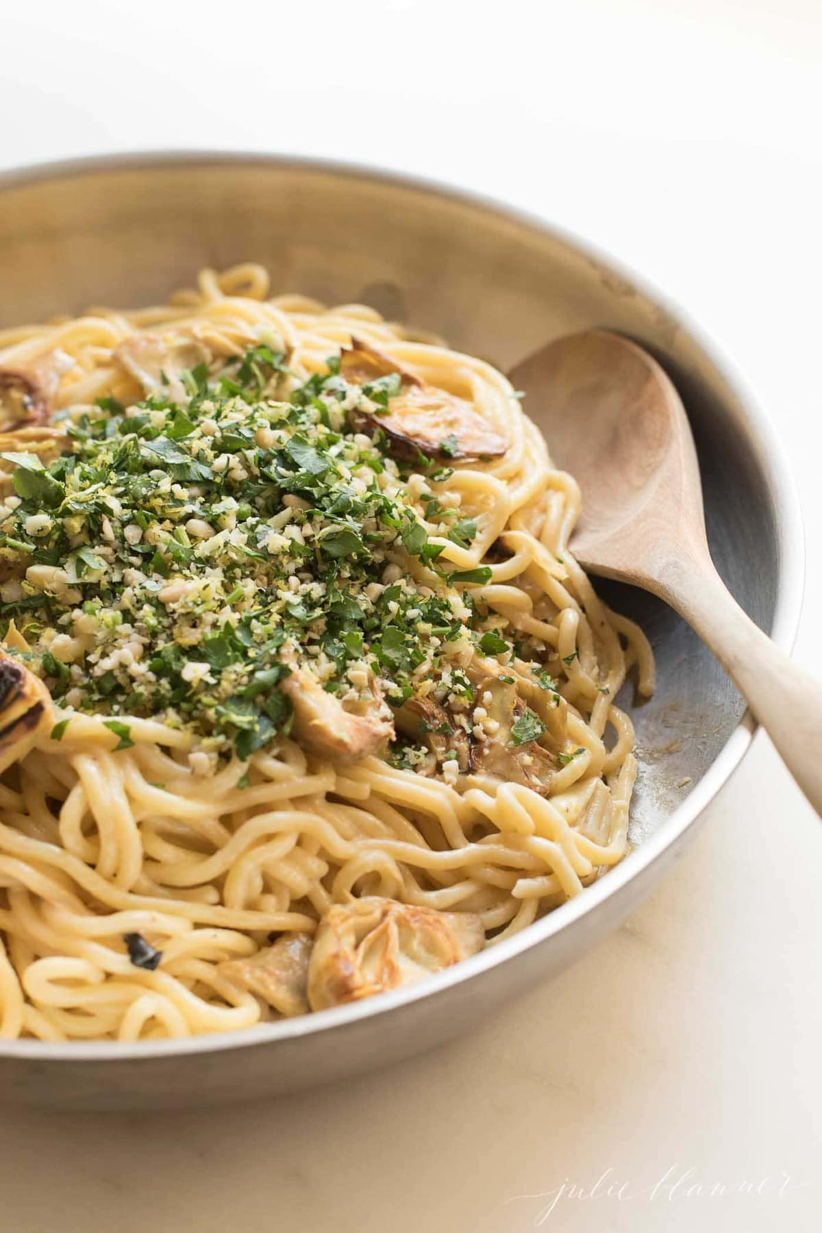 spaghetti in a skillet with artichokes and gremolata with a wooden spoon