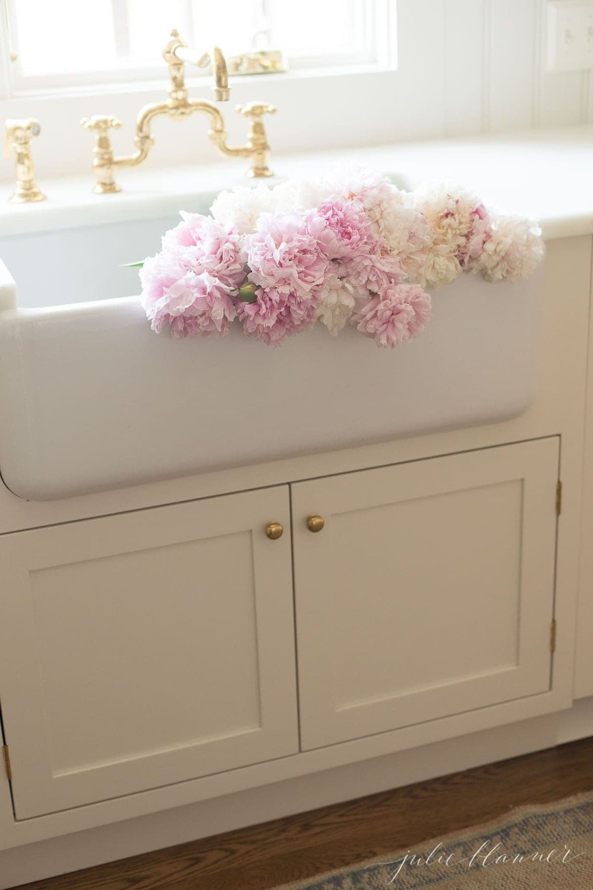 peony flowers draped over the front of a farm sink in a white kitchen.