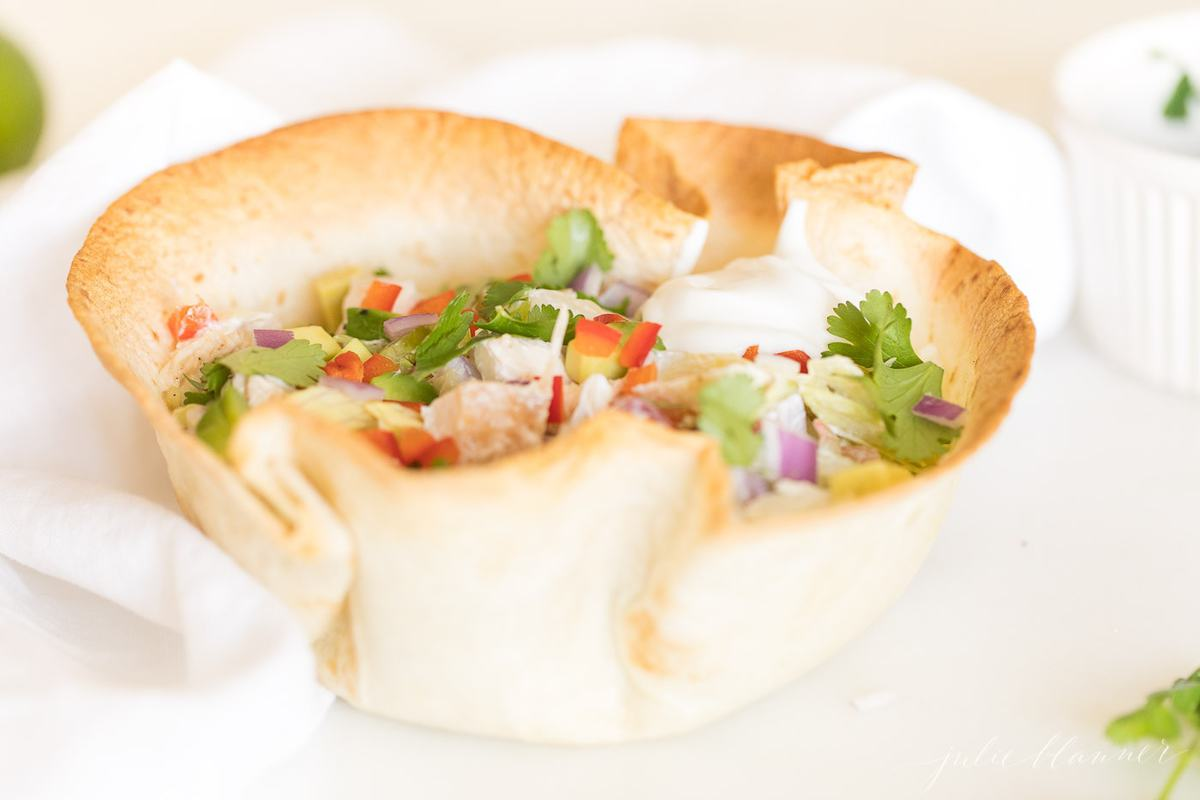A tortilla bowl filled with chicken, lettuce, vegetables and more, on a white surface.