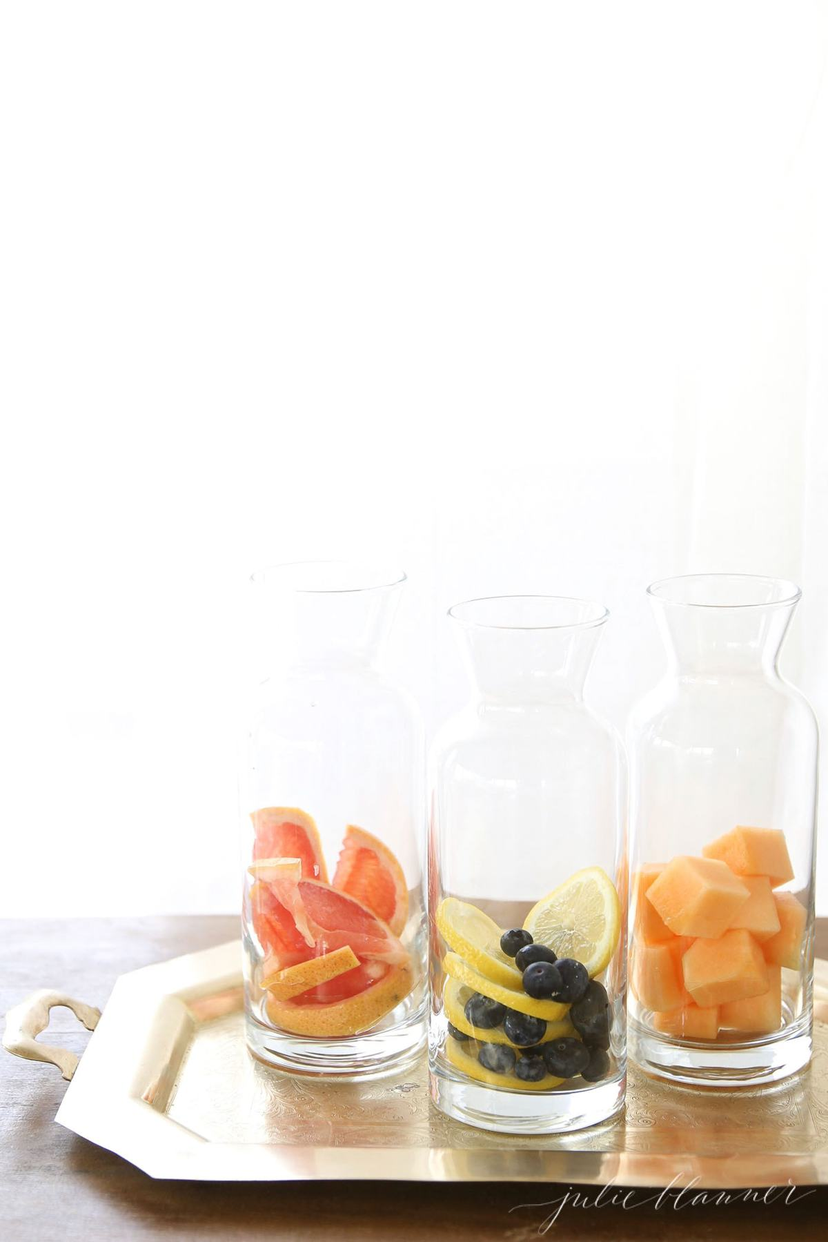 Glass containers full of fruit infused water on a gold tray.
