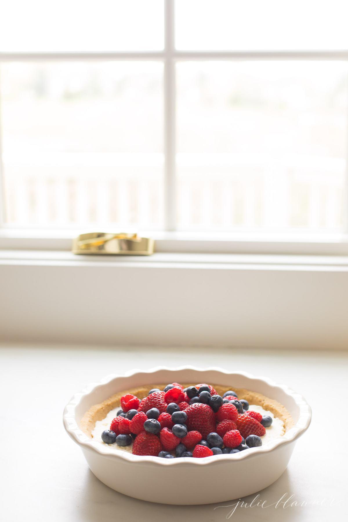 lemon pie with fruit sitting by window