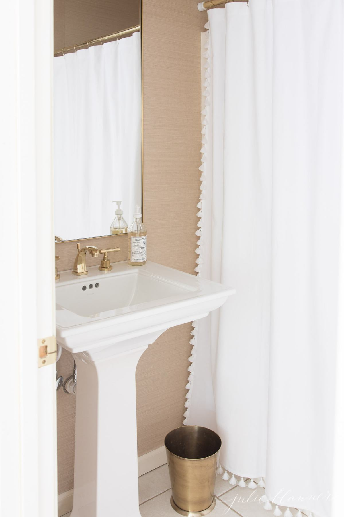 gold bathroom mirror in a bathroom with grasscloth wallpaper for vacation vibes.
