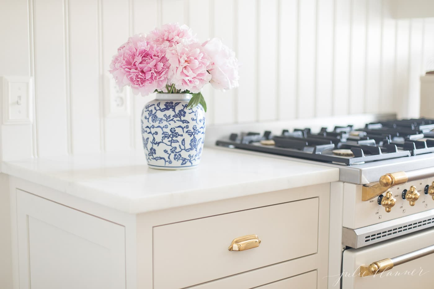 pink peonies in a blue and white vase by a range in a white kitchen.