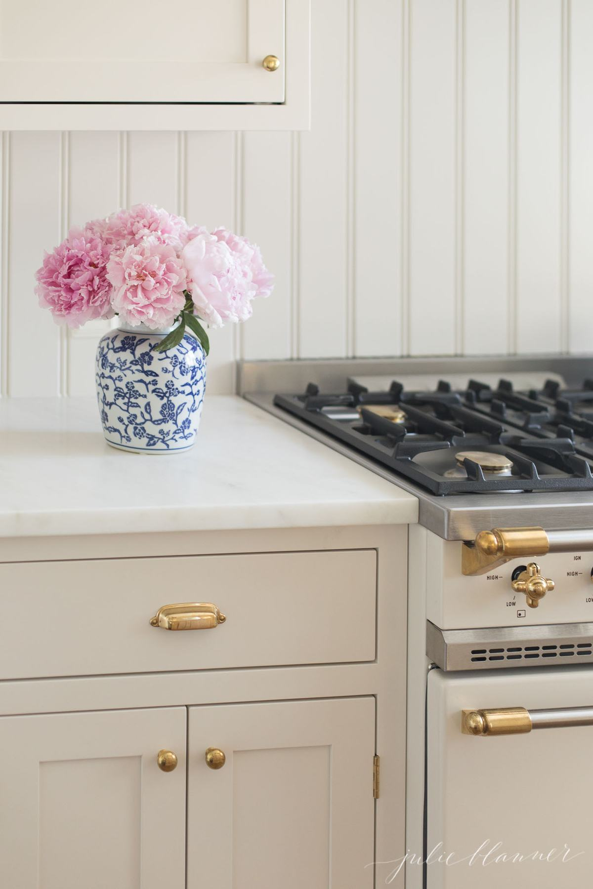 A white kitchen with a blue and white vase of peony flowers by the range.
