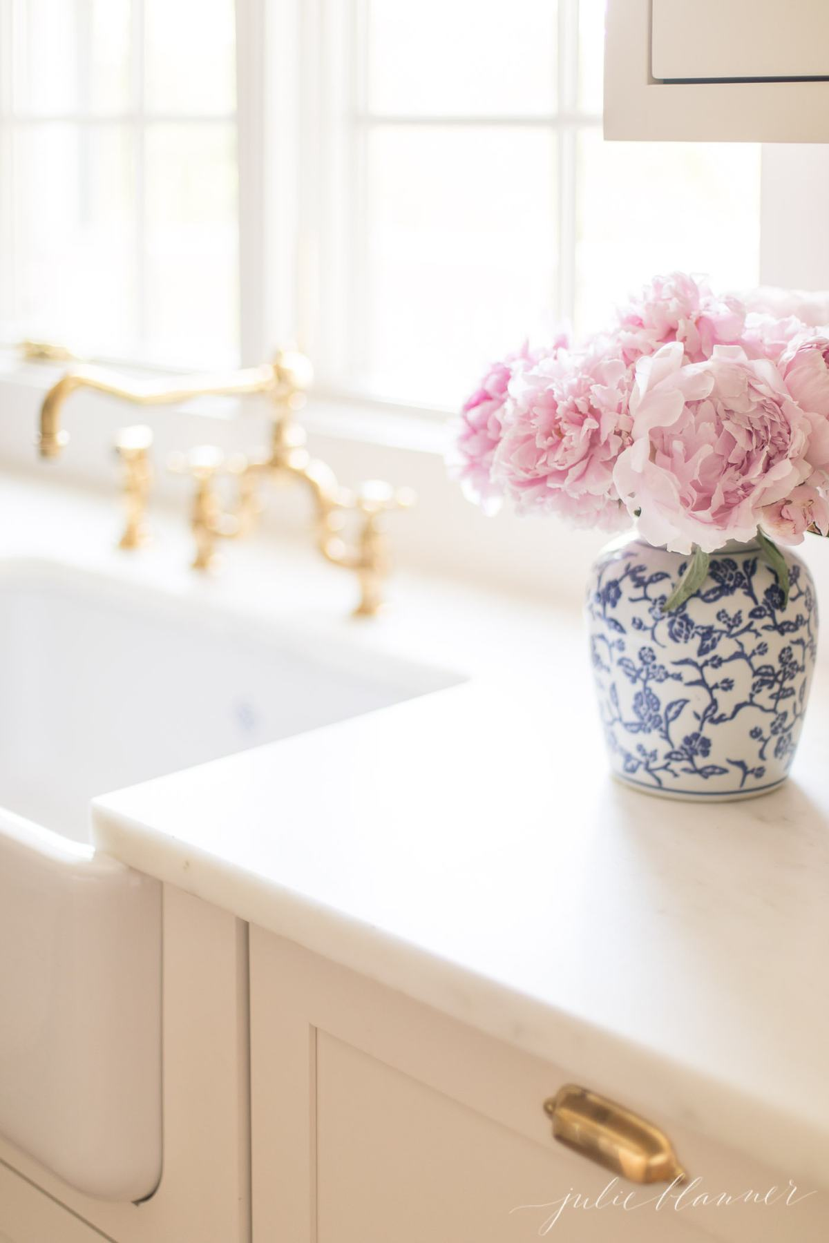 A blue and white porcelain vase of peonies by the kitchen sink.
