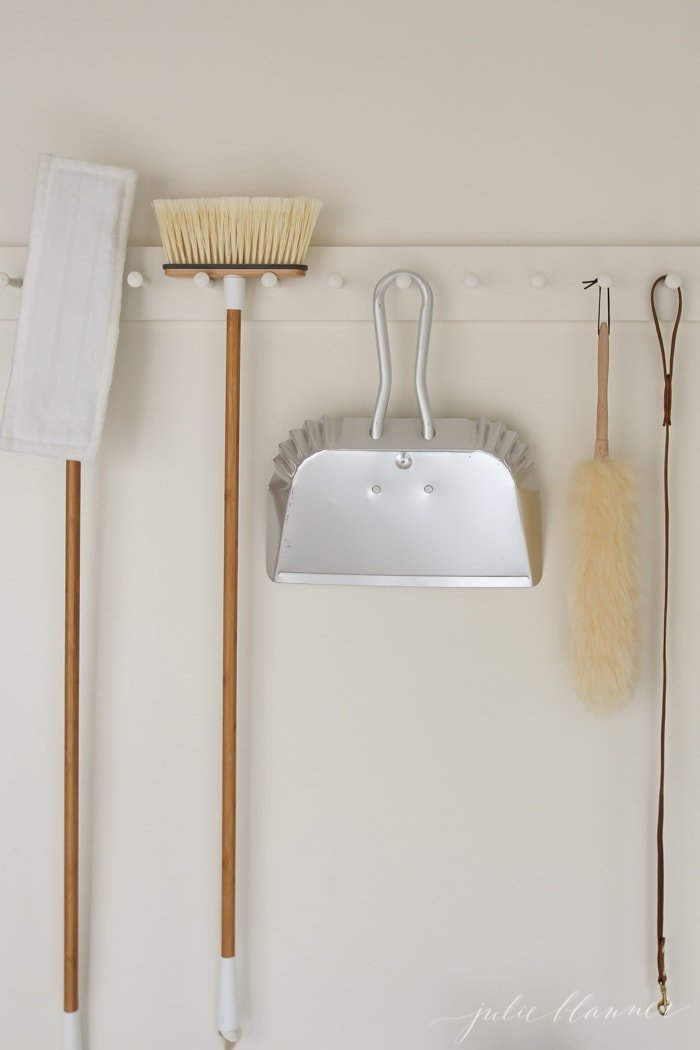 A white painted shaker peg rail holding cleaning supplies in a garage, in a post about how to get rid of smoke smell.