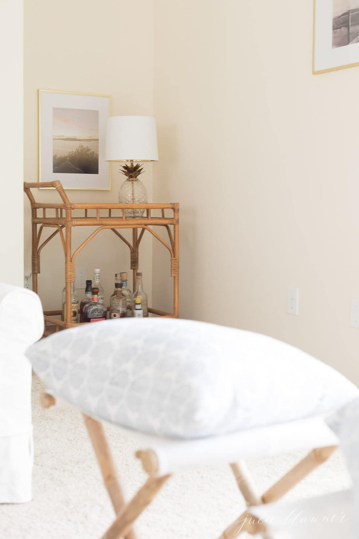 A bamboo style bar cart in a white painted living room.