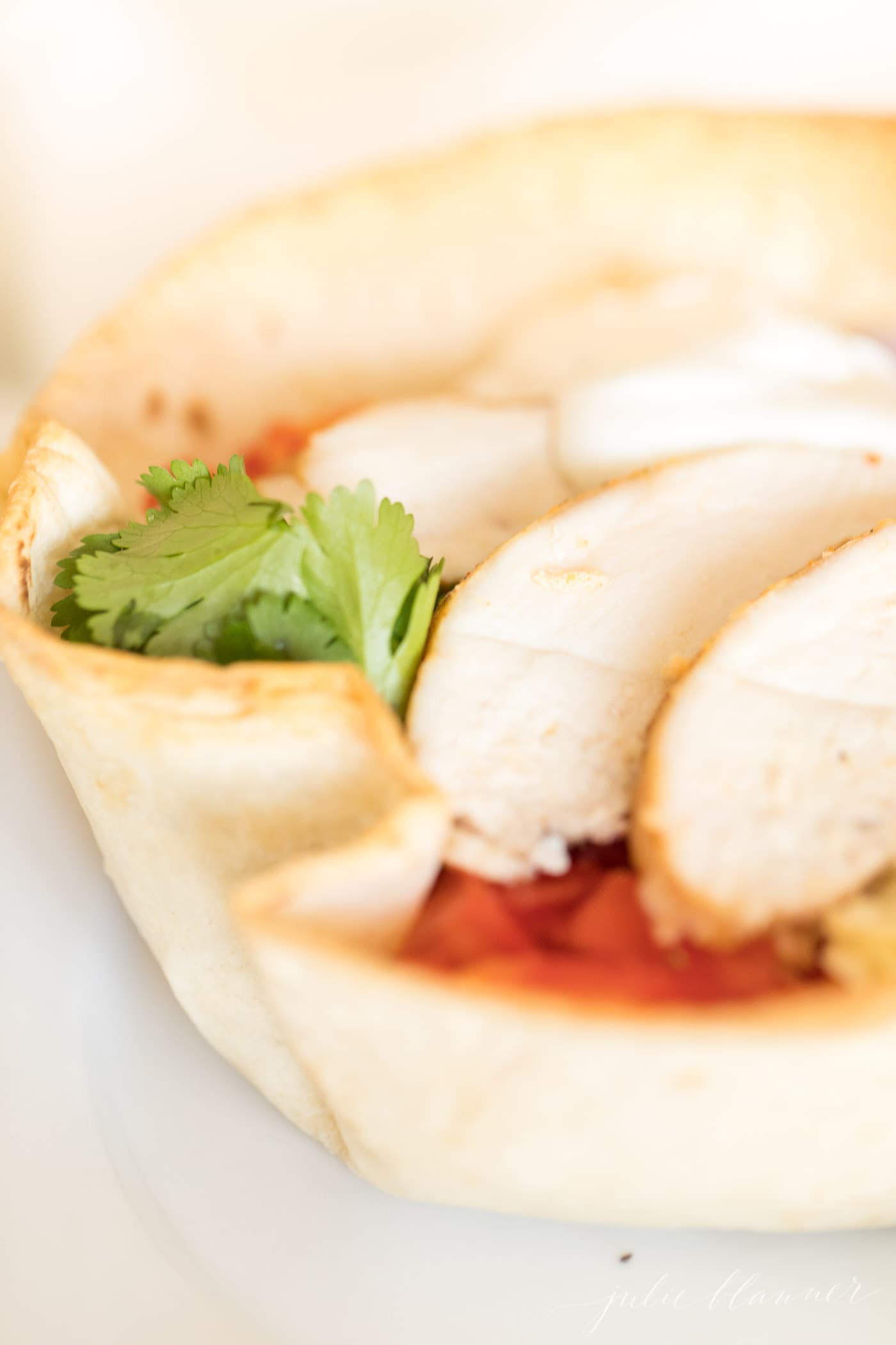chicken taco salad in a tortilla bowl on a white plate