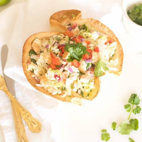 A chicken taco salad on a white surface, gold silverware and cilantro to the side.
