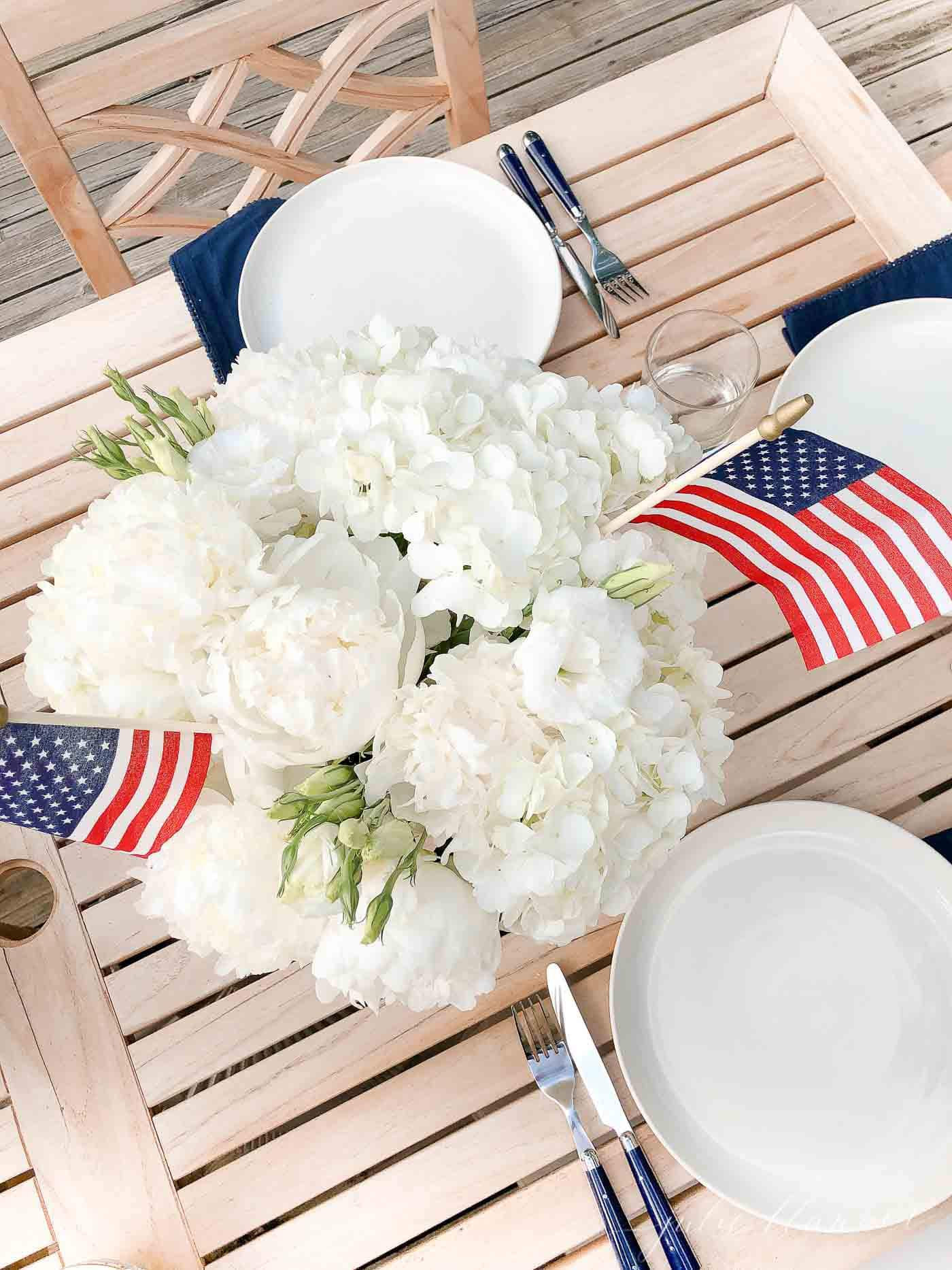 4th of july flags in a white hydrangea centerpiece on a teak outdoor table.