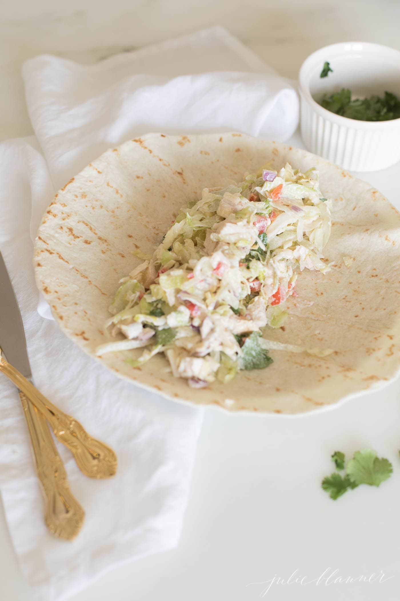 chicken lettuce and other ingredients on open tortilla