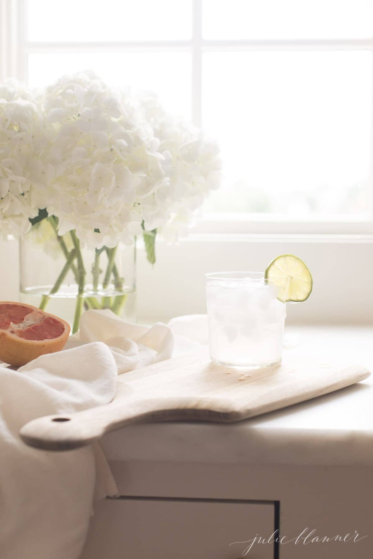 A cutting board with a fresh paloma drink on top, floral arrangement in background.