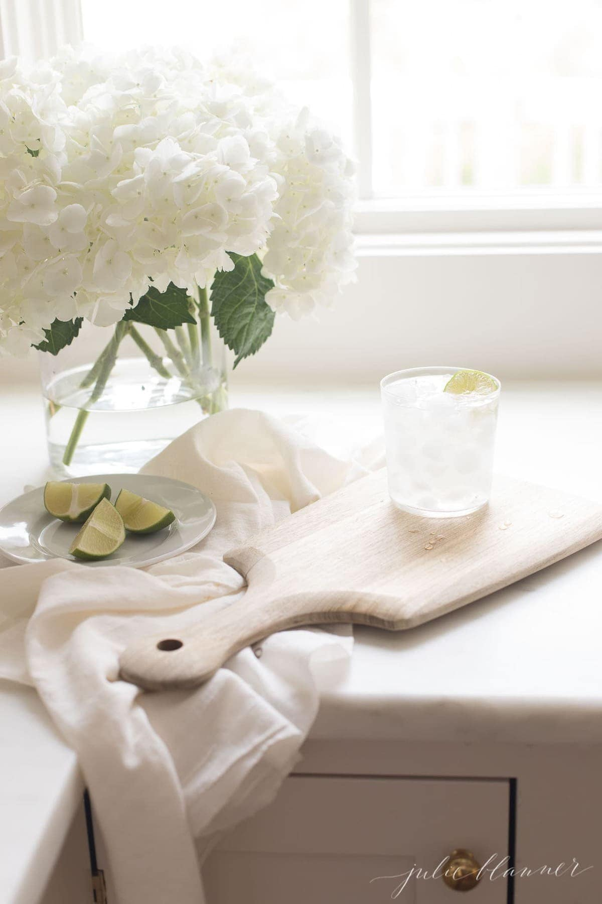 White surface with a glass filled with a paloma cocktail recipe on ice.