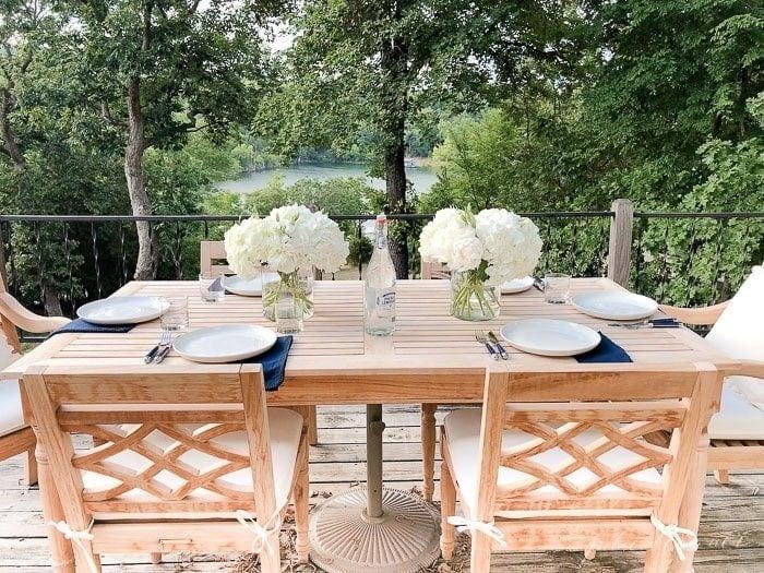 hydrangea centerpieces on a teak table on an deck.