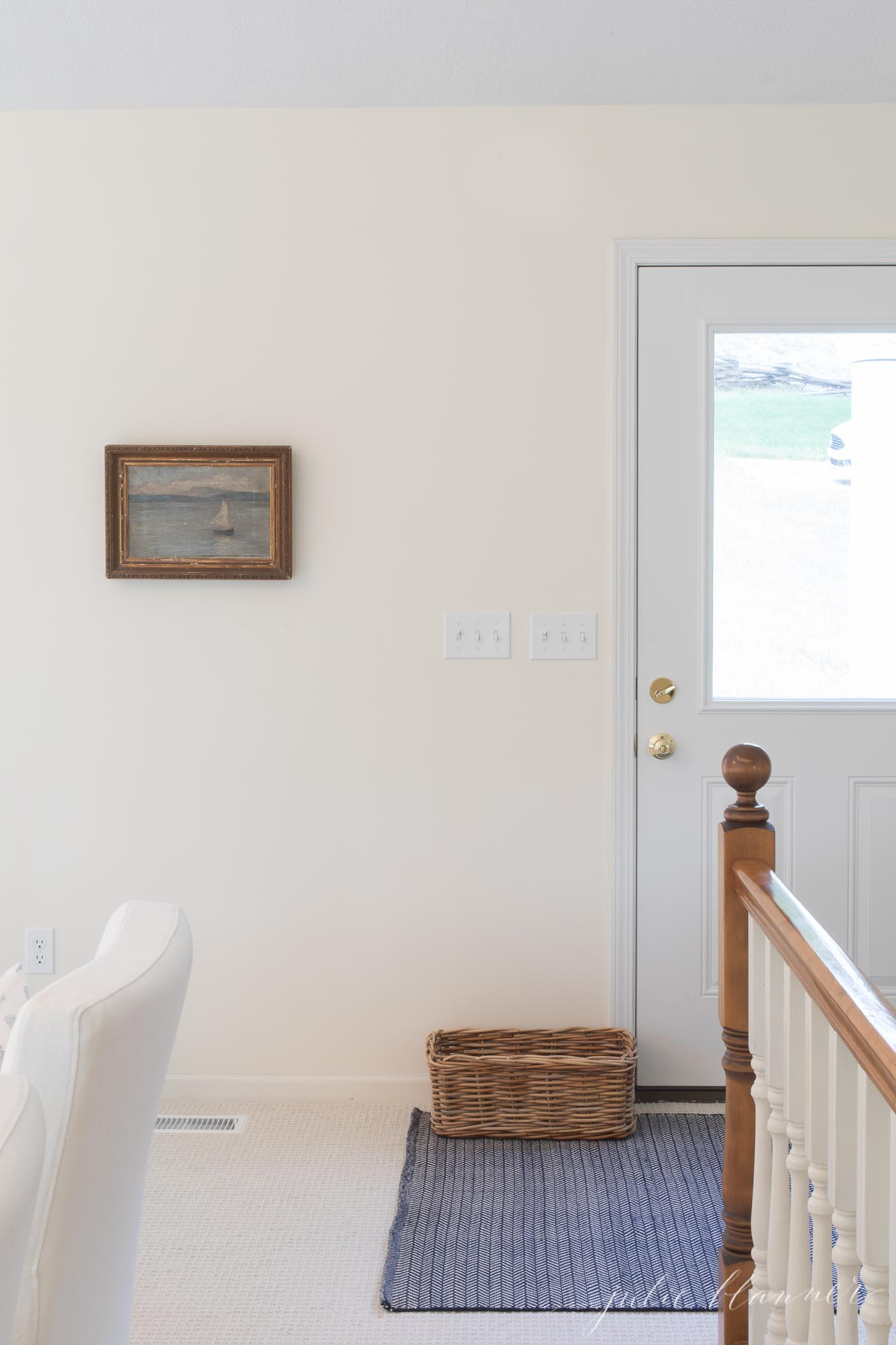 entryway with white door blue rug and sailboat painting