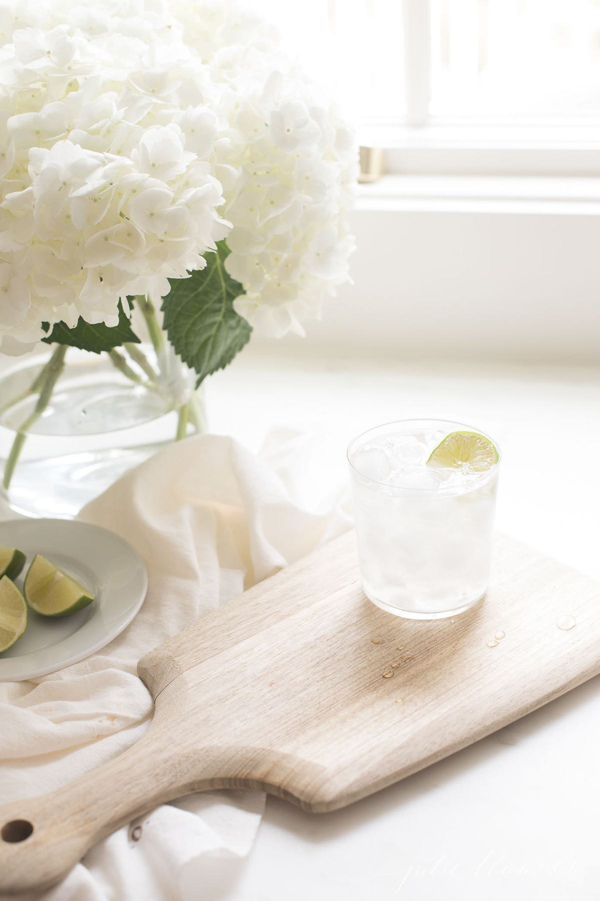 A fresh paloma recipe in a clear glass on ice, with a vase of fresh flowers in the background.