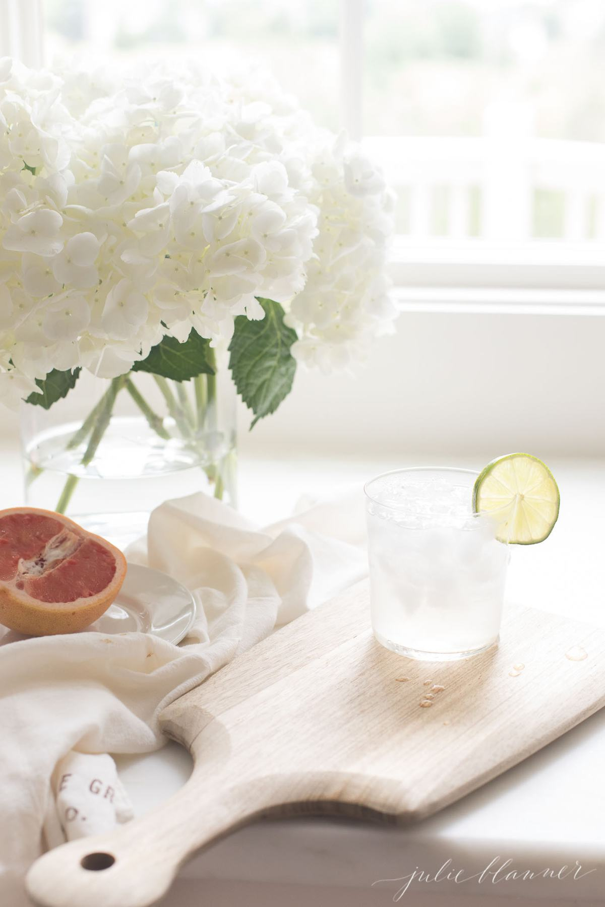 A paloma cocktail in a kitchen with a white flower arrangement in background.