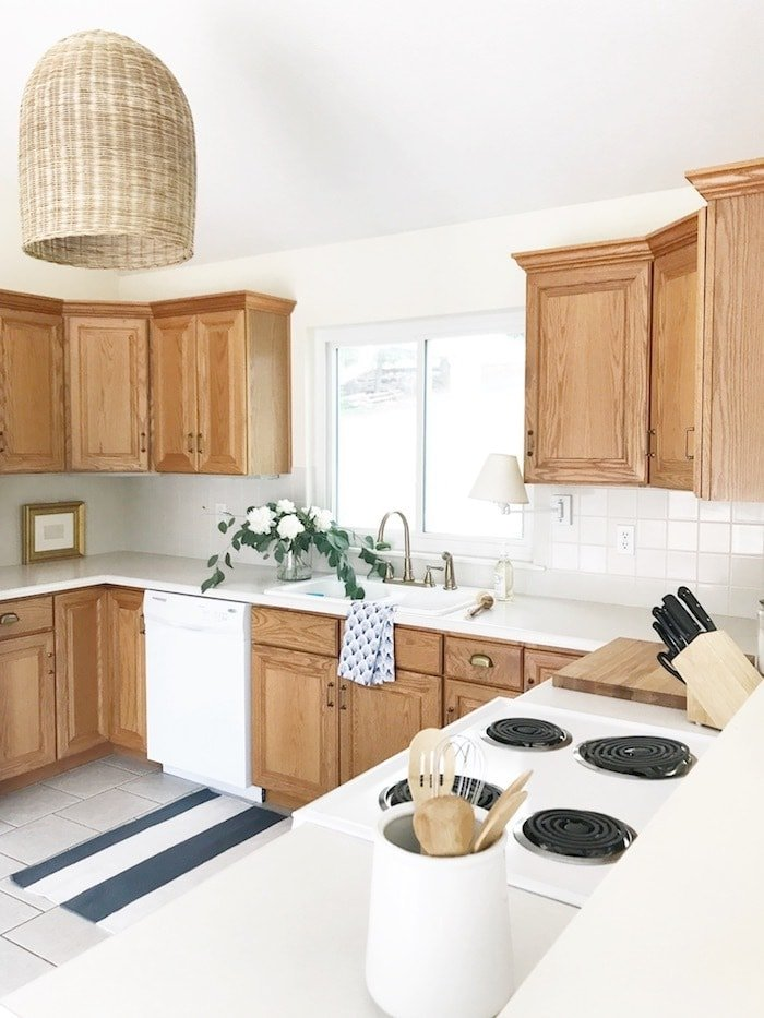 wood overlay cabinets in kitchen with pendant light and stripe rug
