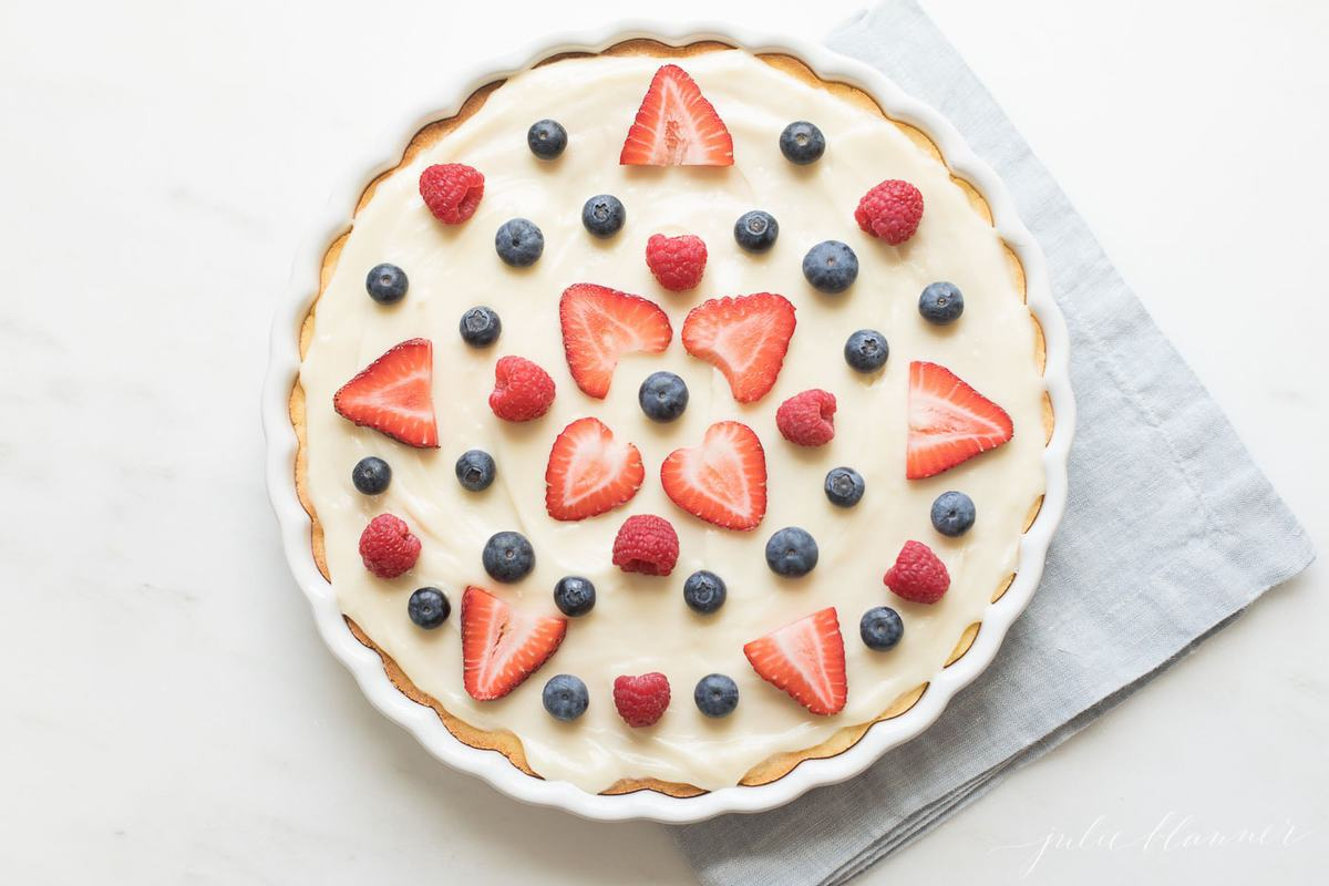 A round sugar cookie cake covered in berries with a blue napkin to the side.