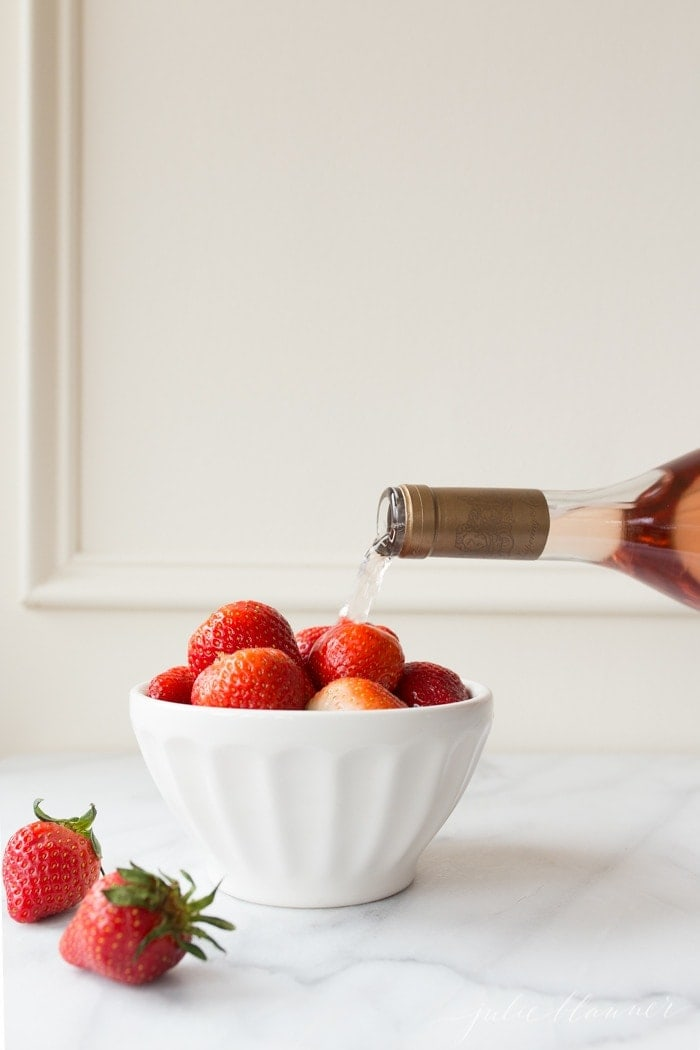 A bowl of straberries, with a bottle of wine being poured over the top.