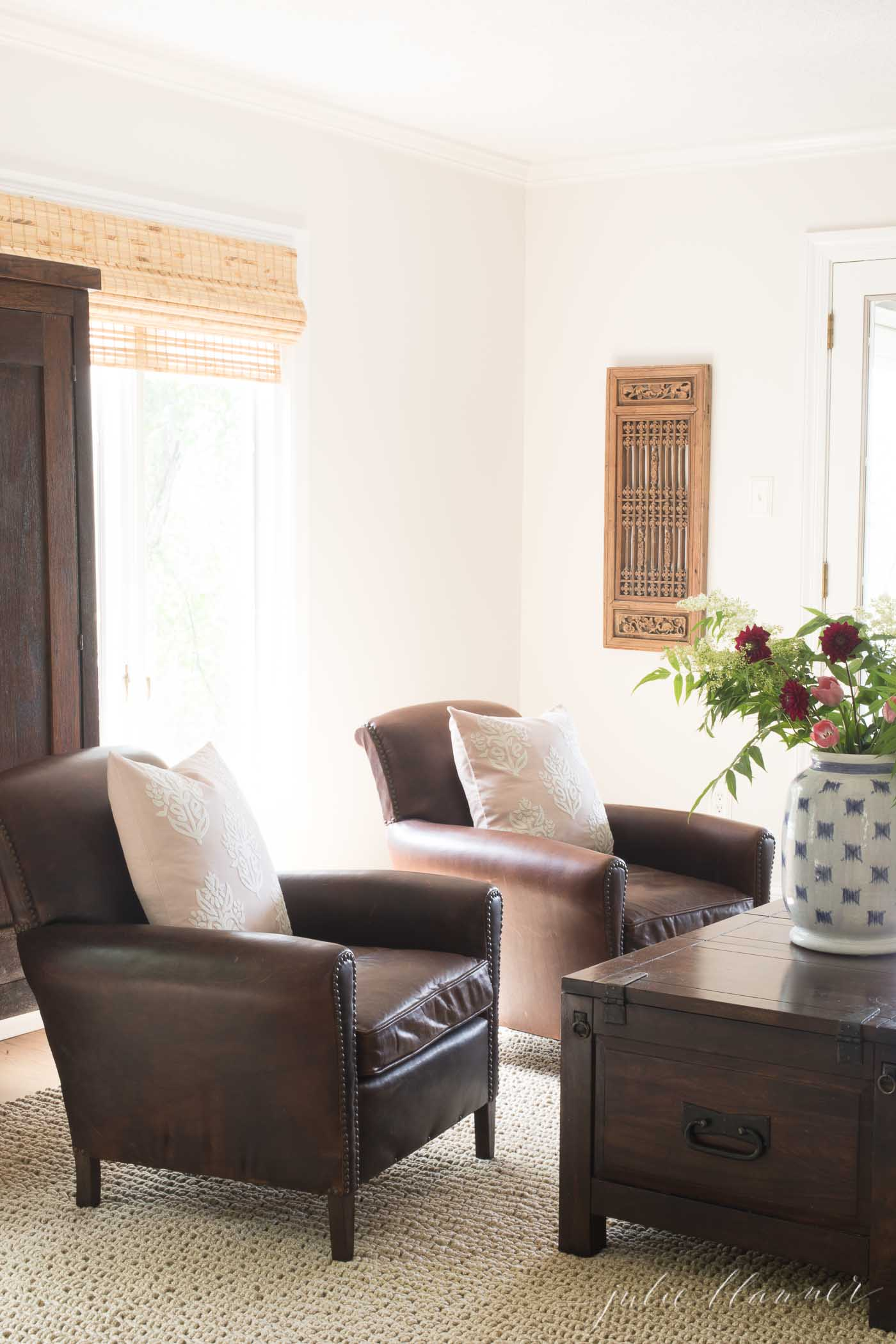 A natural looking kid friendly rug in a living room, with leather chairs and a dark coffee table.