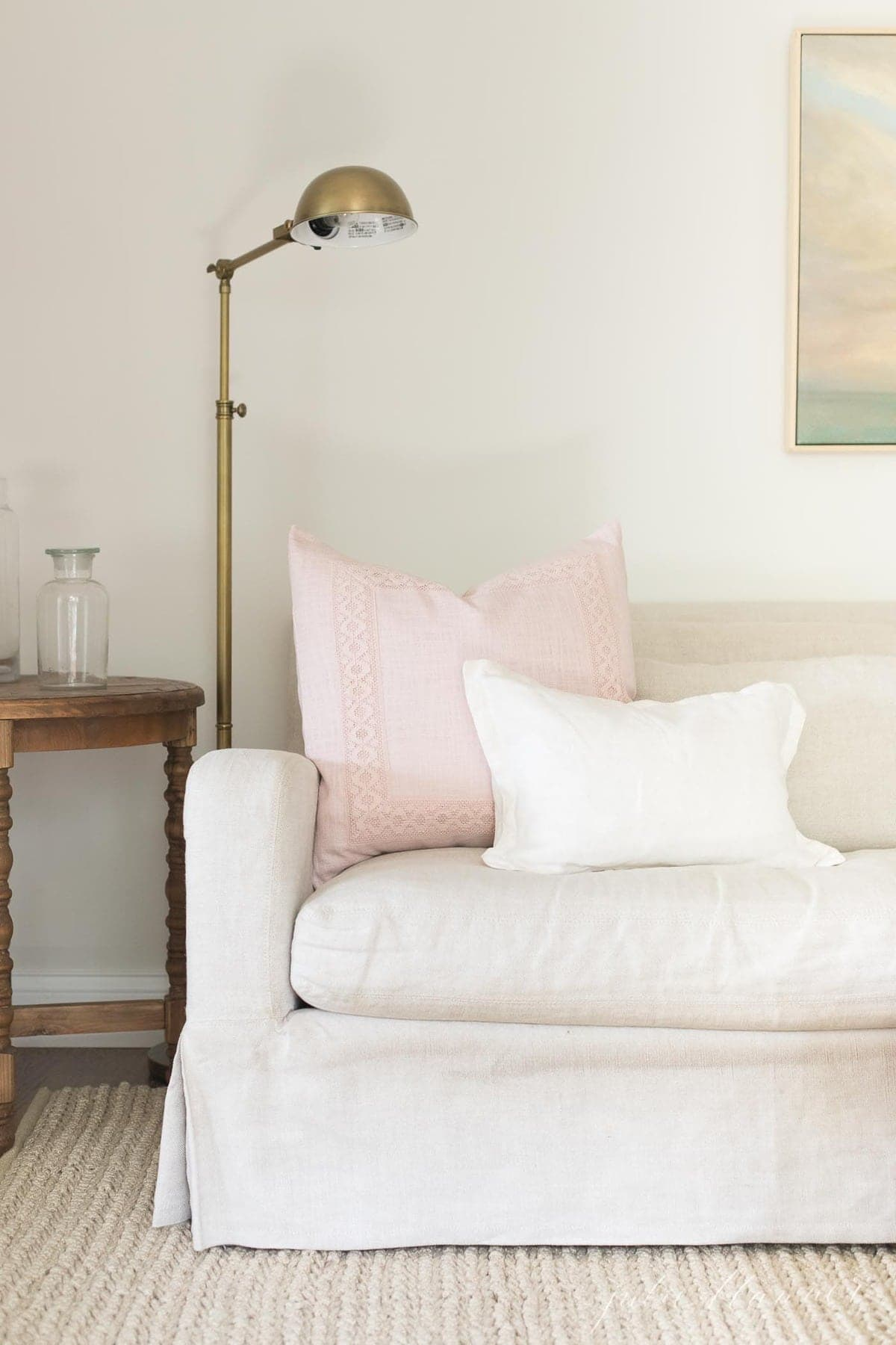 A soft cream living room with a linen sofa and a beige rug.