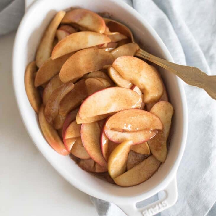 A white oval baking dish filled with baked apple slices, gold spoon coming out the side.