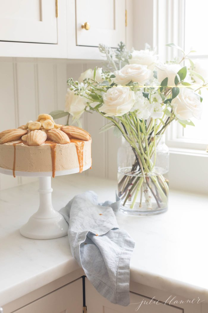 A banana cake on a stand next to flowers