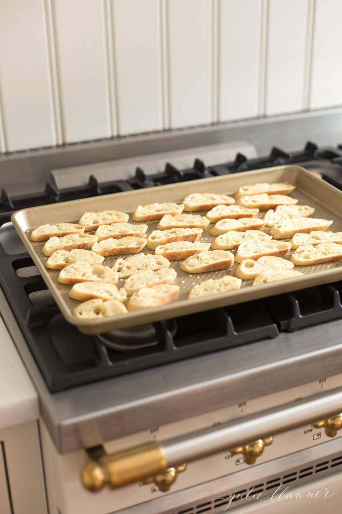 Crostini slices on a gold sheet pan on top of a range.