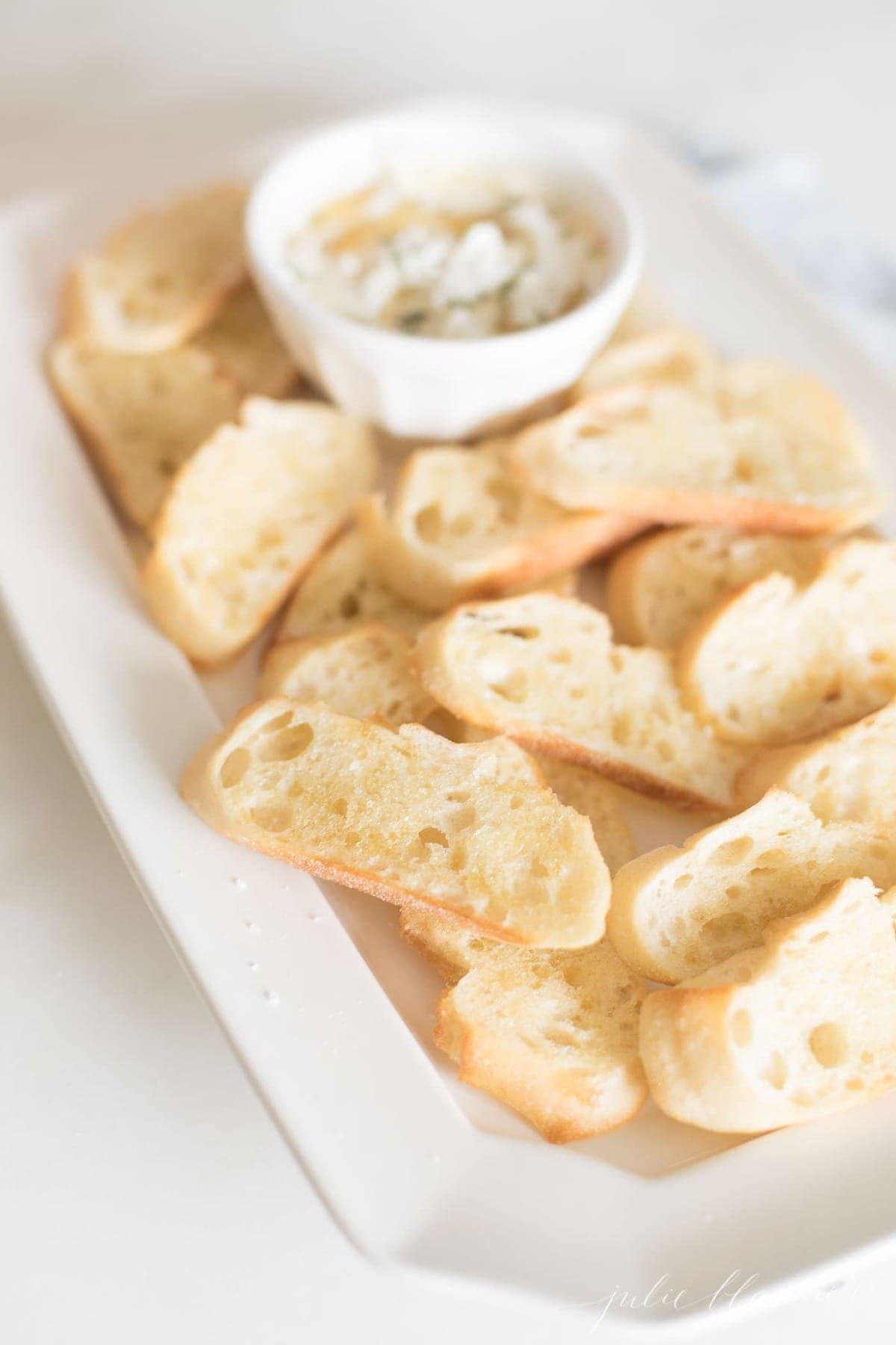 crostinis on a white platter next to dip