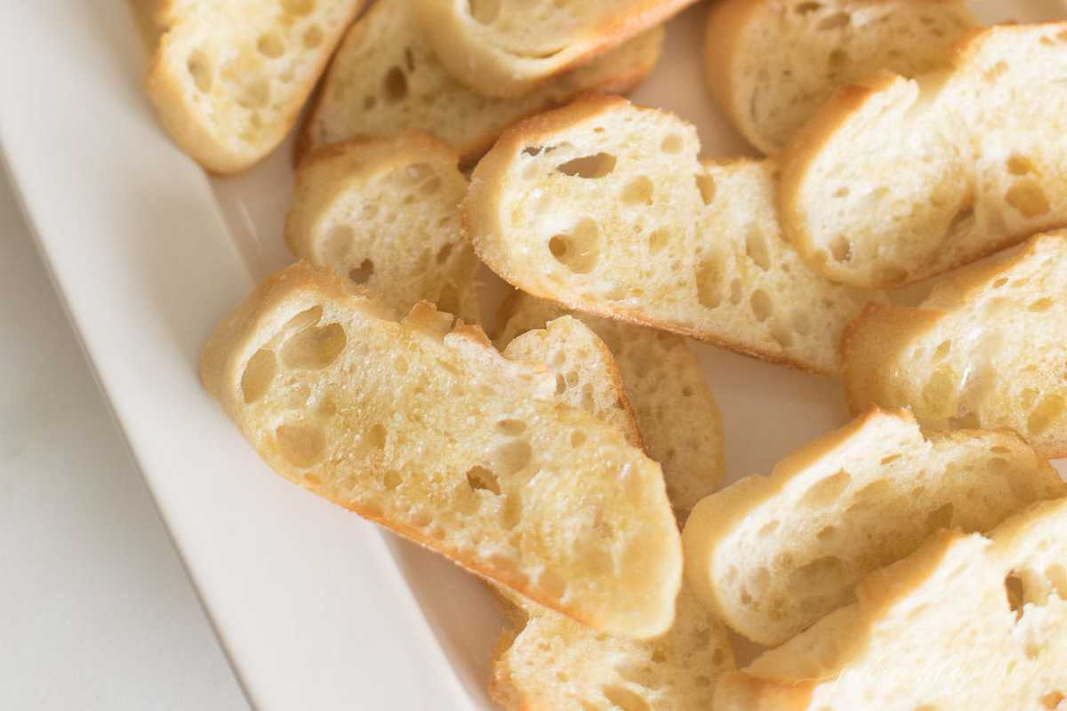 crostini brushed with olive oil on a white platter
