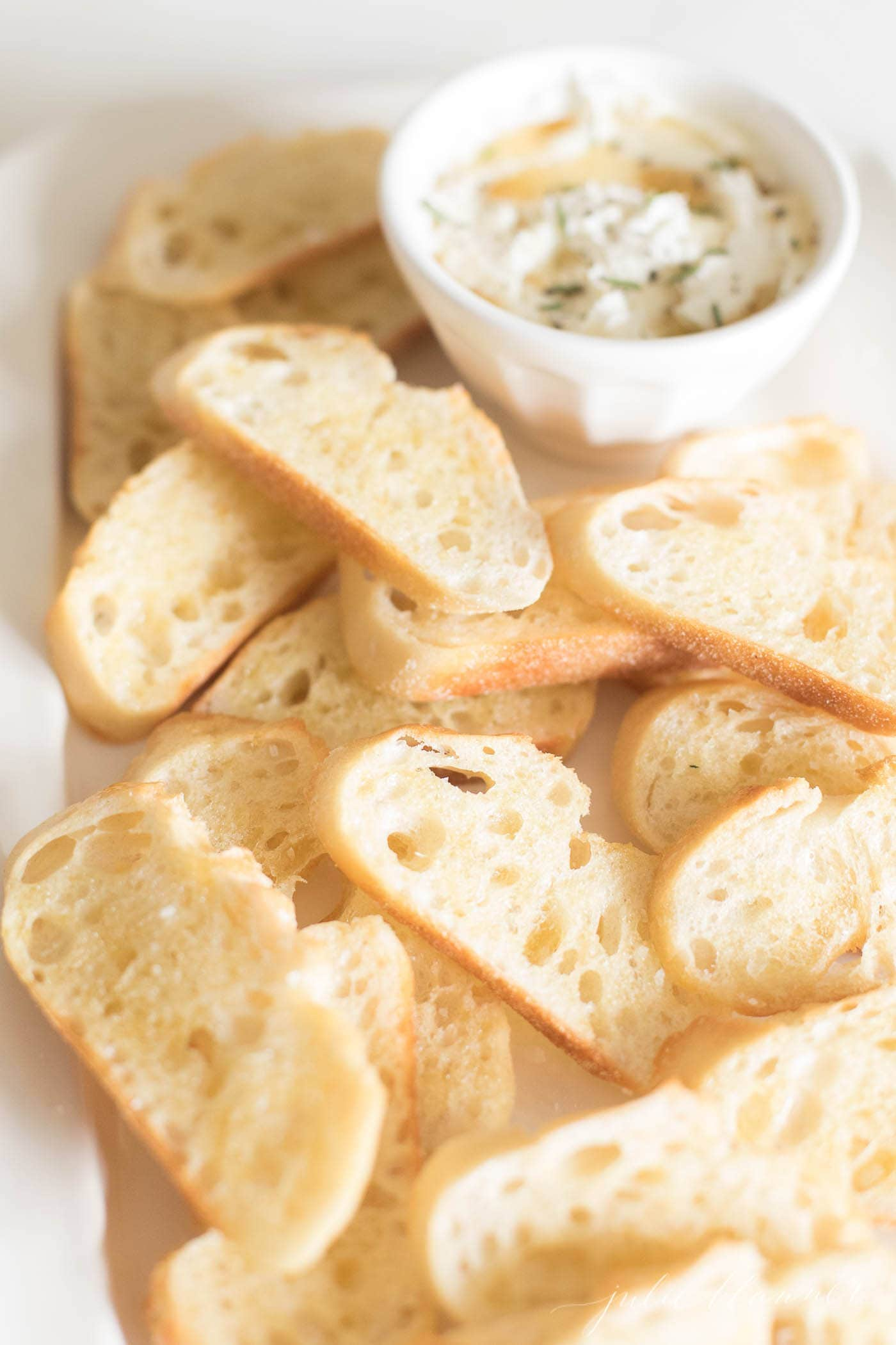 crostini slices on a white platter, dip in background
