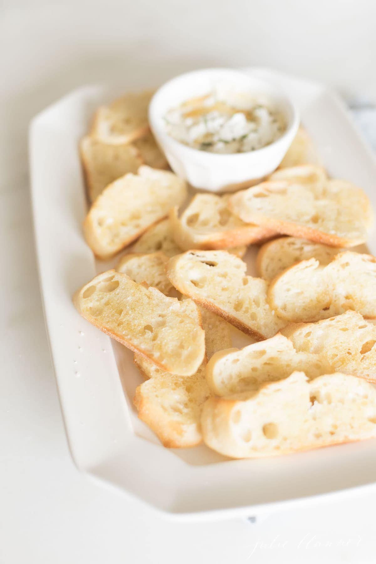 crostini on platter with dip in a white bowl