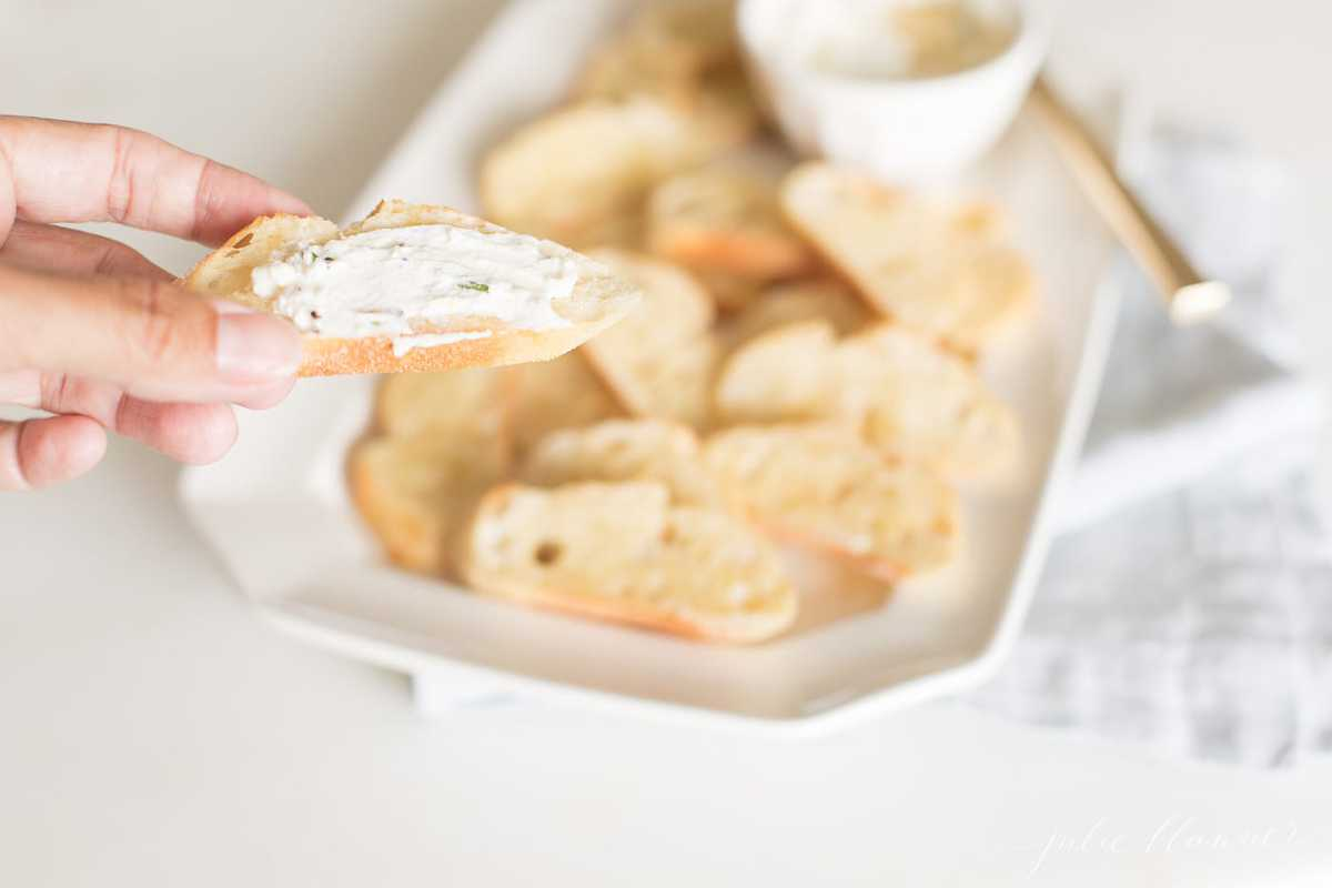 A hand holding a slice of crostini topped with whipped goat cheese, platter of crostini in the background.