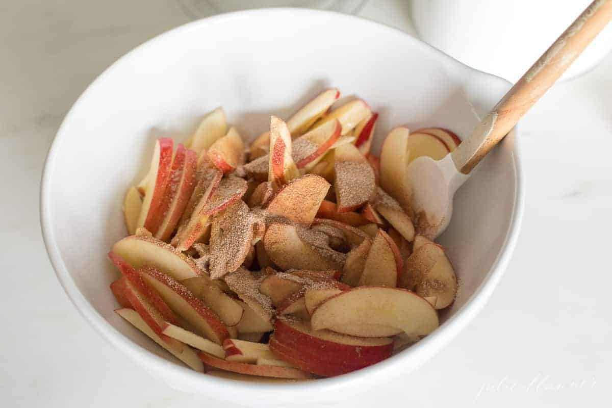 apple slices covered in butter cinnamon and sugar in a mixing bowl