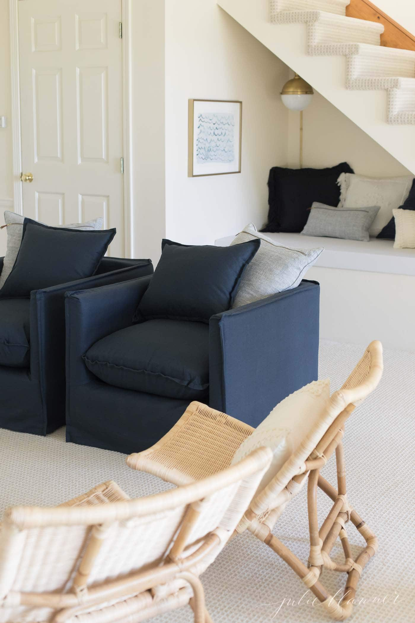 modern living room with navy chairs and rattan chairs