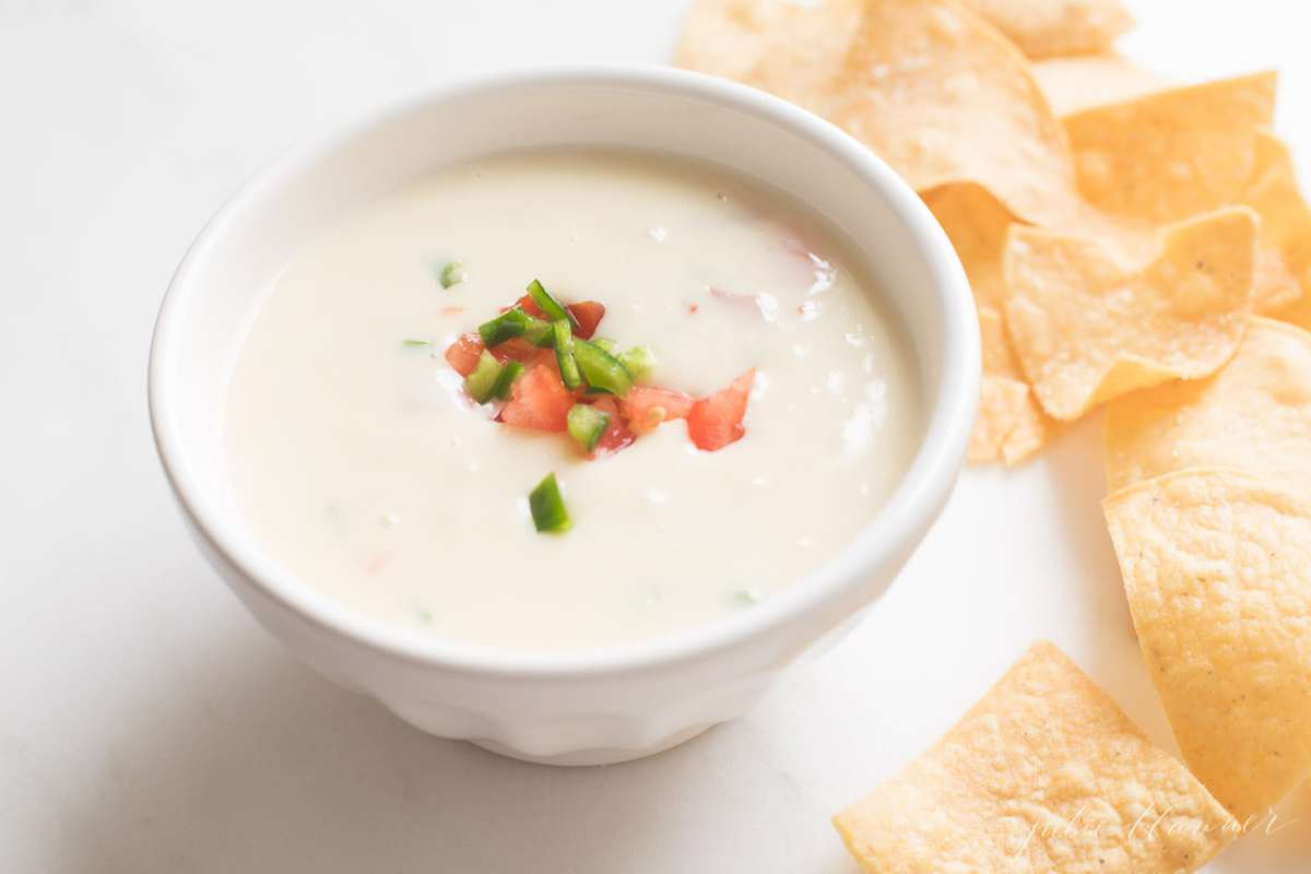 queso blanco dip in a white bowl with tortilla chips