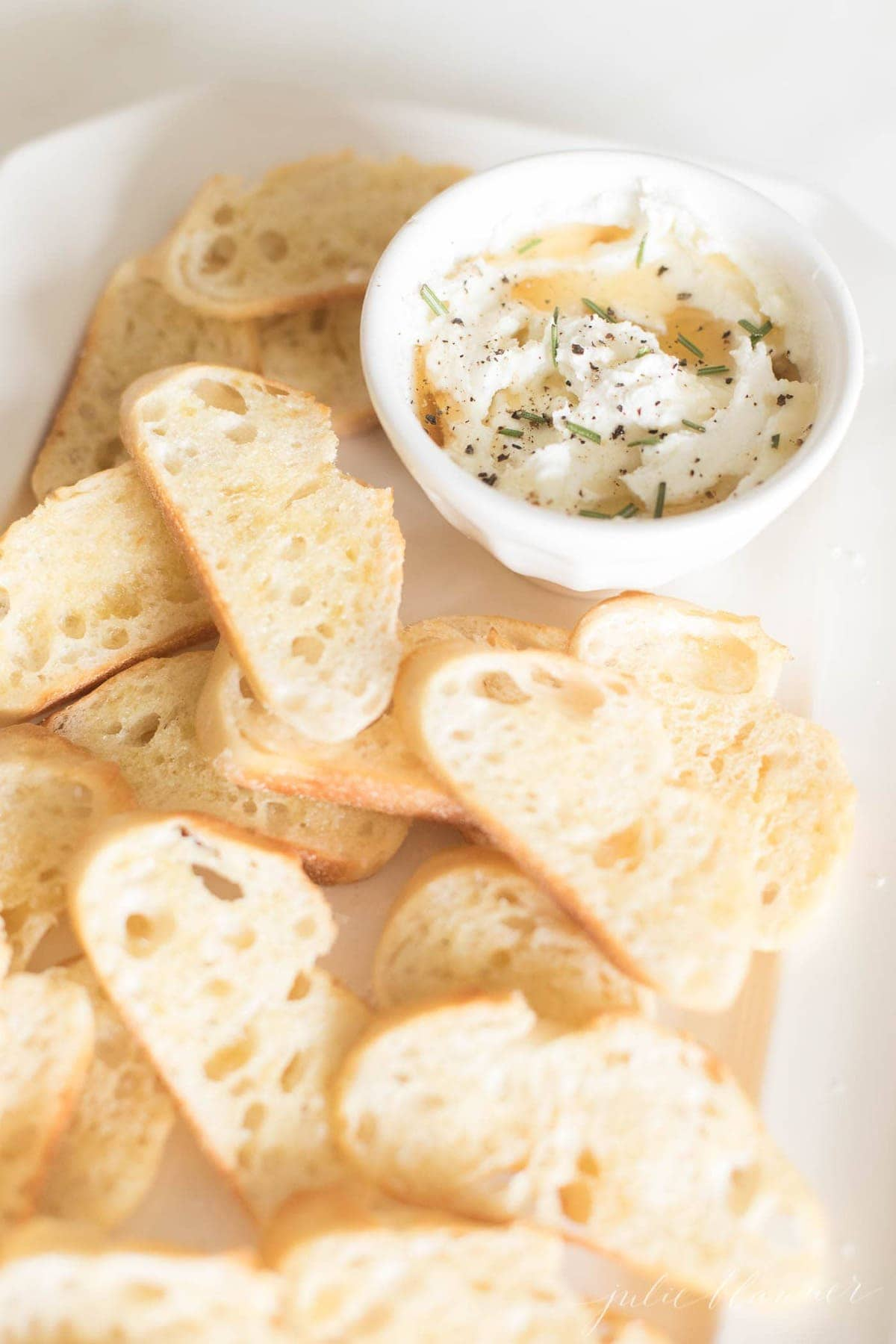 Whipped goat cheese spread in a white bowl on a white platter full of sliced crostini.