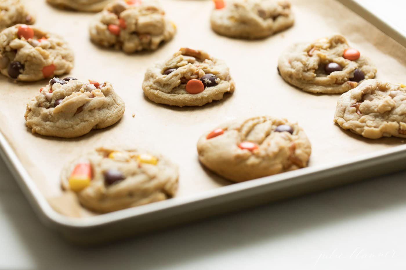 A baking pan covered in fresh baked cookies from a monster cookie recipe.