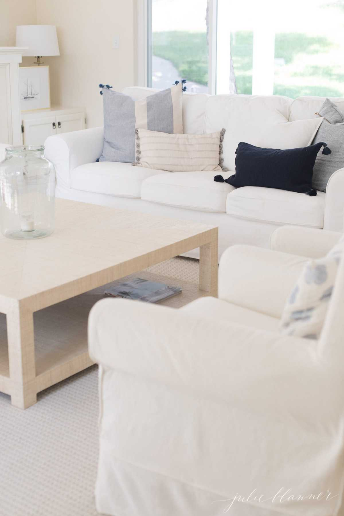 A white living room with a white sofa and blue pillows.
