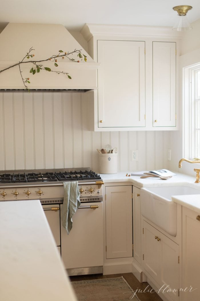 cream kitchen with crabapple branch on range hood