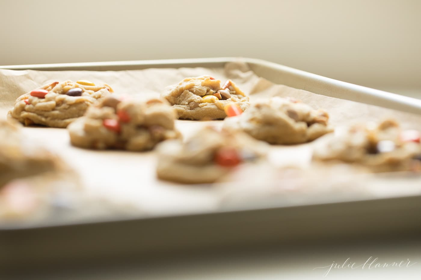 monster candy cookies on a gold sheet pan with parchment paper